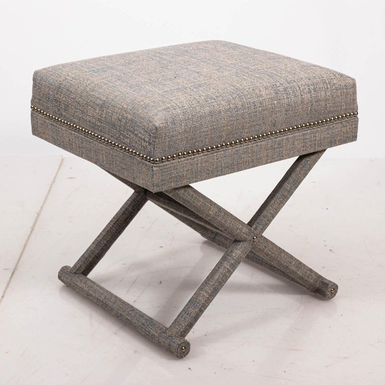 Upholstered X-frame bench with fabric cushion and metal nail head trim. Please note of wear consistent with age.