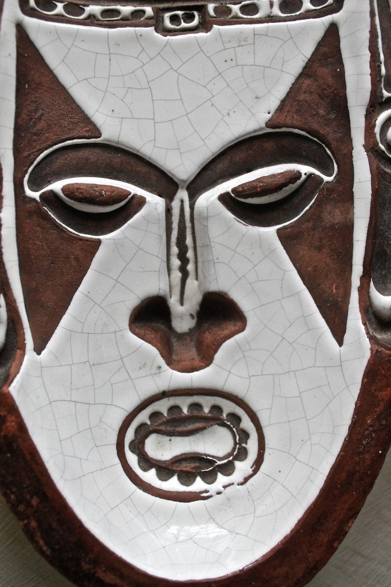 A low intaglio relief of a tribal mask, white crackle glaze on brown fired clay. Remnants of painted signature on bottom.