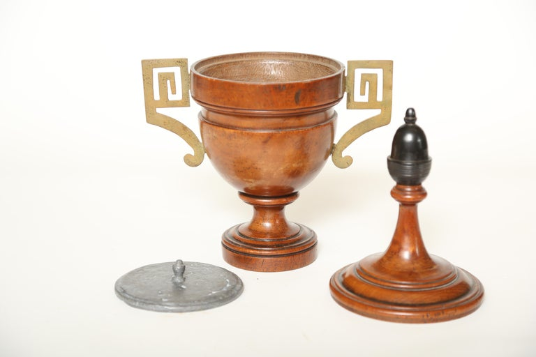 Urn shaped treen tobacco jar. The beautifully patinated wood is topped by a long necked lid with an ebonized acorn finial. The Greek key style handles are brass. The interior contains a lead weight to hold the tobacco in place. An unusual item for