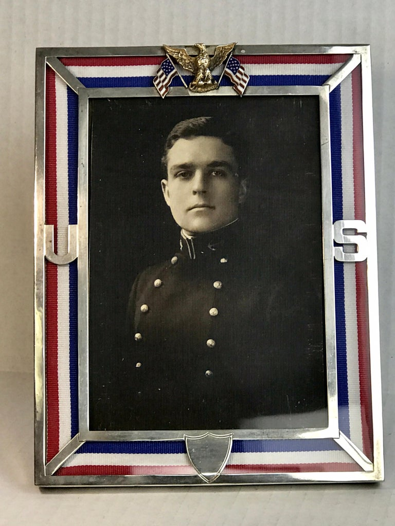 Theodore B. Starr, Inc Sterling and 6-karat gold United States Military frame with red, white and blue ribbon detail, holds a 4.5