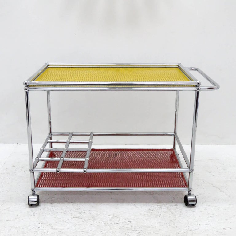 Stunning bar cart by Fritz Haller & Paul Scharer for USM Haller, two-tier modular chrome frame on casters with unique red and yellow powder-coated perforated metal shelves, frame includes eight bottle compartments, can be extended with additional