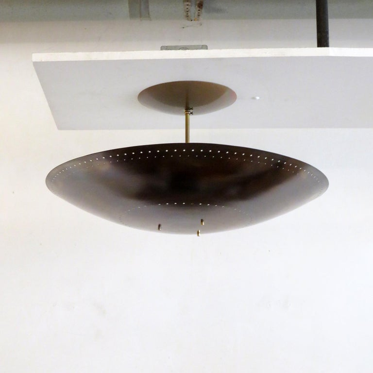 Large-scale ceiling flushmount light Utah-24 designed by Gallery L7, handcrafted and finished in Los Angeles from American brass,bsuspended perforated raw brass disc (24inch diameter). Six E12 sockets per fixture, max. wattage 40w each, wired for US