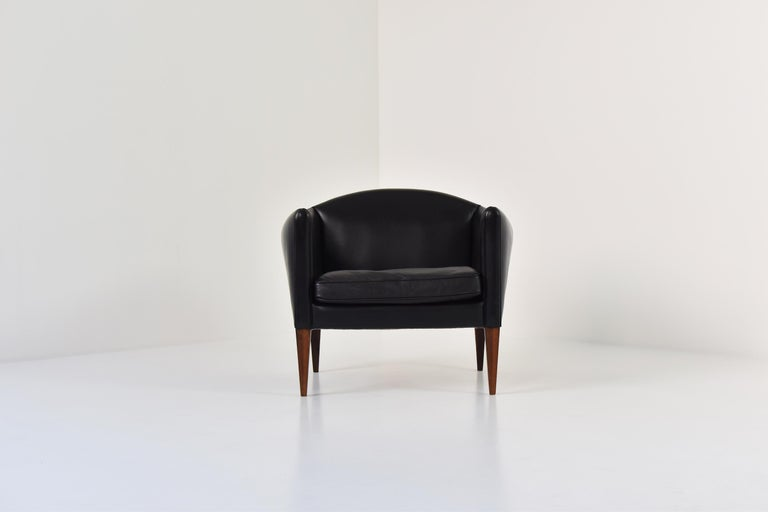 Lovely V12 easy chair by Illum Wikkelsø for Søren Willadsen Møbelfabrik, Denmark, 1960s. This elegant side chair features a black leather upholstery and marvelous shaped rosewood legs. Very good original condition.