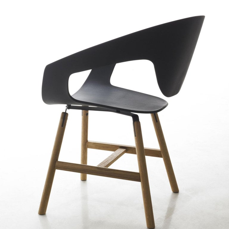 This set includes two Vad chairs raised on walnut-painted oakwood legs with a black reinforced polypropylene shell seat (43.5 cm high) inspired by the iconic Scandinavian style. Comfortably large and elegantly shaped, this modern chair designed by