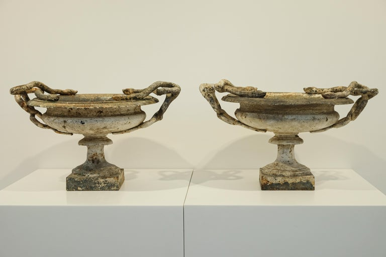 """A small pair of white cast-iron urns with intertwined snakes. Marked with a """"1"""" to denote the smallest of three sizes made by the renowned Val d'Osne Foundry. The smallest size is particularly rare. Exquisite tones of white, brown, and rust with a"""