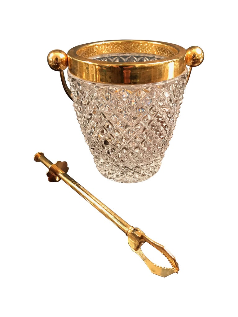 A Val St Lambert crystal ice bucket with gold plated rim and handle, with gilt metal ice grabber.