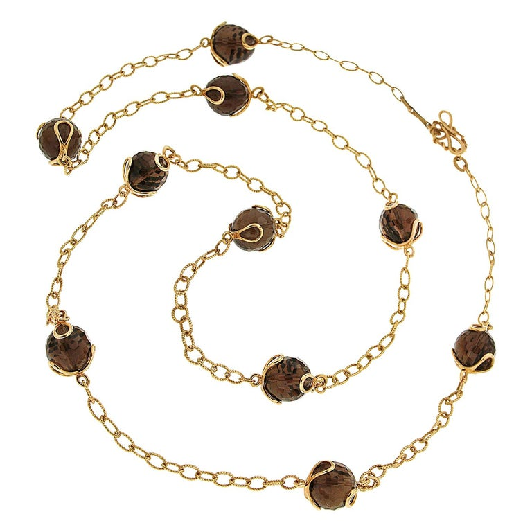 This lovely Carina necklace features 10 Smoky Topaz balls in 34'' chain with knots and toggle clasp in 18kt yellow gold. Modern and Chic, adds sophistication and depth to your outfits.