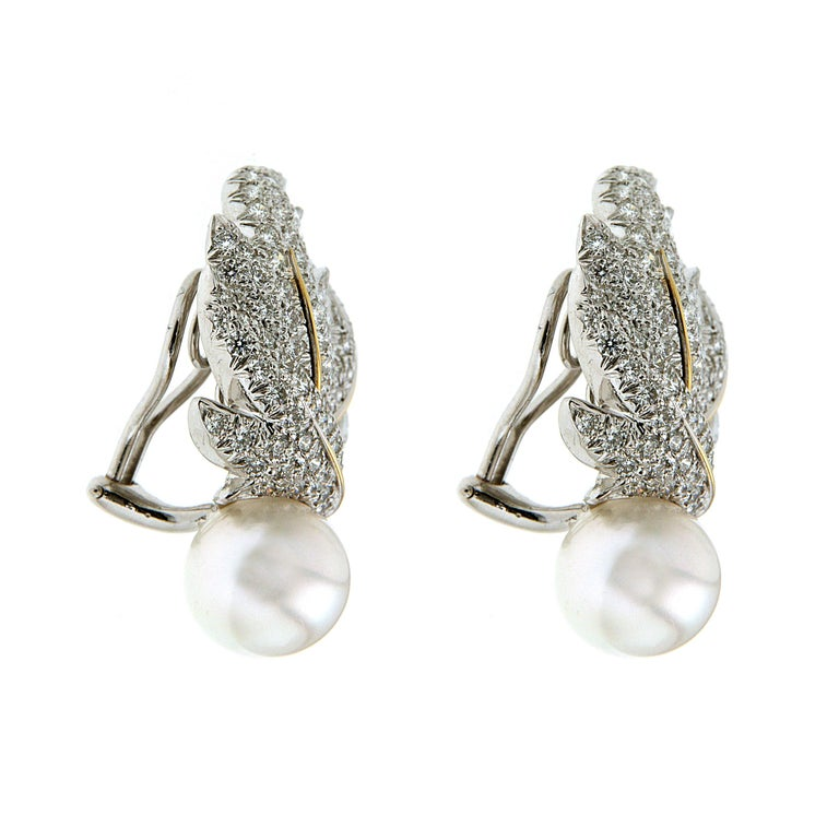 Diamond leaves and pearls adorn these earrings. The upper portions feature 18k white gold leaves covered in pave set round brilliant cut diamonds and yellow gold stems. Round pearl drops make up the bottom halves. The 380 diamonds total 6.82 carats.