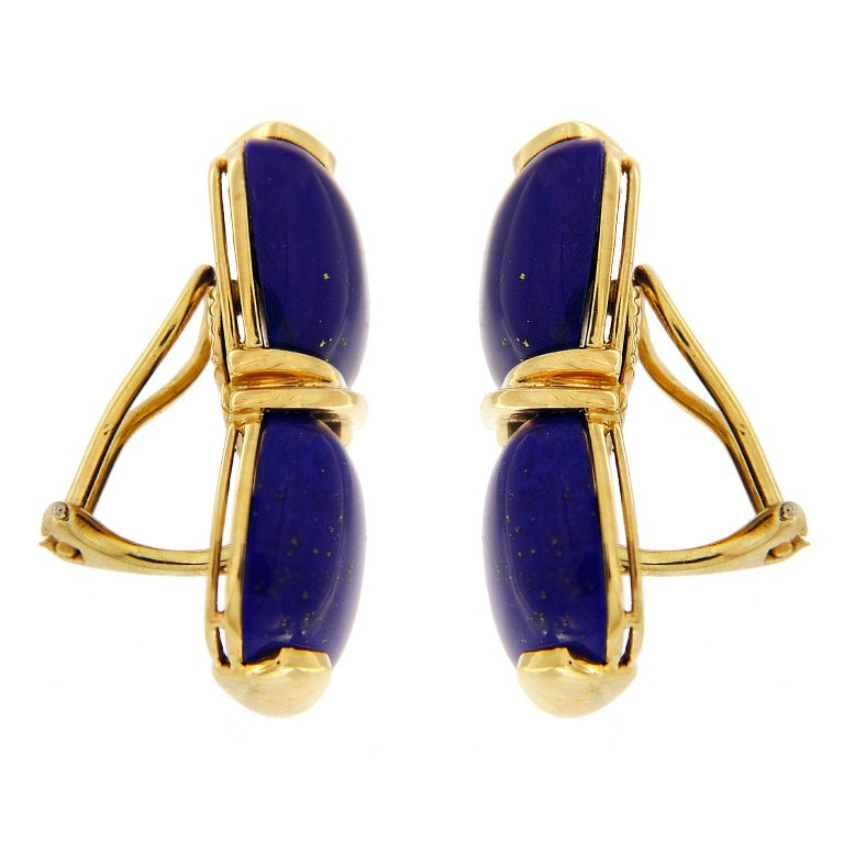 Blue and gold adorn these earrings created by Valentin Magro. The bodies are lapis lazuli carved into cushion shaped cabochons. These are mounted two to an earring, with an 18k yellow gold crisscross in between. This gives the impression of a single