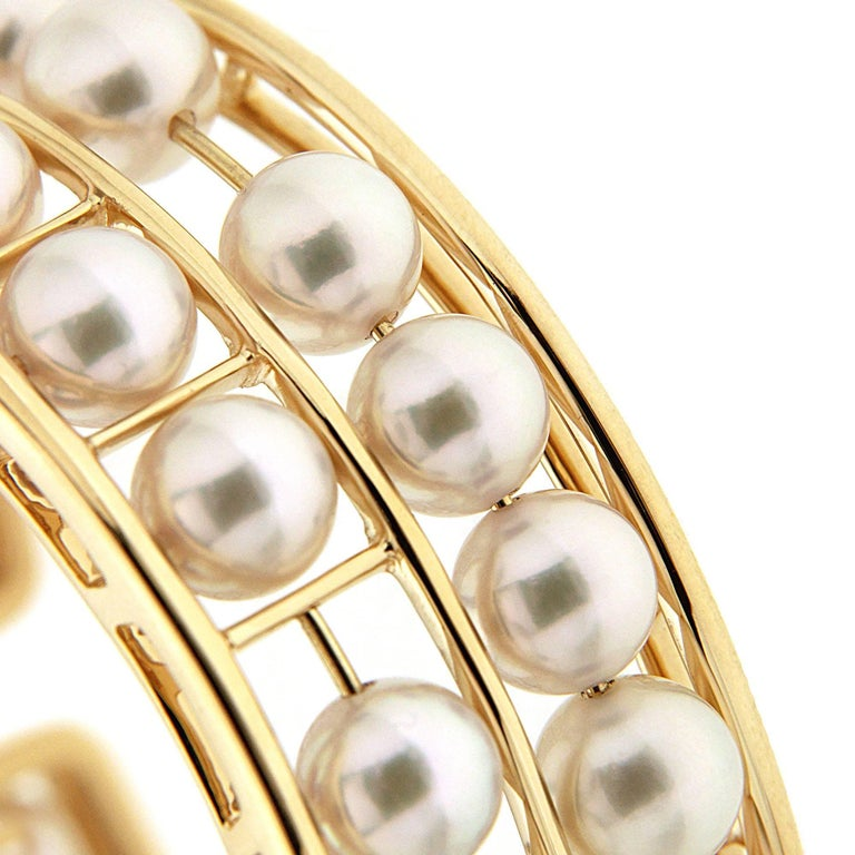 Valentin Magro Pearl 18 Karat Yellow Gold Cuff Bracelet is filled with jewels. The frame is 18k yellow gold divided into two rows and smaller chambers within. Between the outlines shine round white Akoya pearls. At first glance, the gems seem to