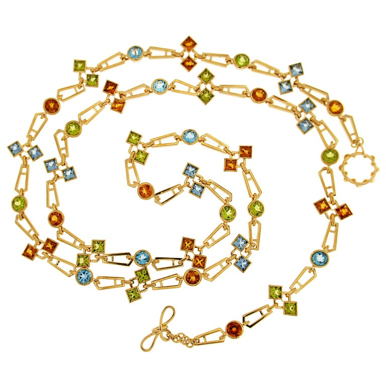 Valentin Magro Geometric Color Stone Chain Necklace showcases bright gems. The body is 18k yellow gold links, with one end of each piece wider than the other. In between are gold circles, supporting either round stones or twin princess cut jewels.