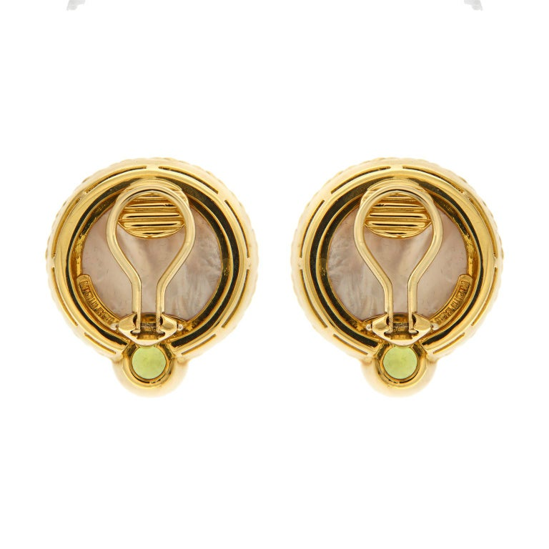 These earrings are made in 18kt yellow gold, they feature a round faceted peridot and baroque pearl blisters, the backs on these earrings are clip-backs.