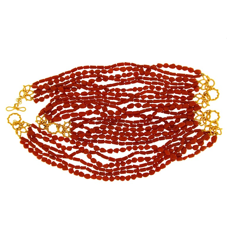 Red and gold adorn this necklace. The former comes from coral shaped into elongated beads and strung on six rows twisted into one. There are four sets of beads with interlocking 18k yellow gold Vs in between, adding bright contrast. A knot and