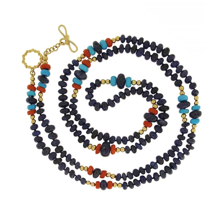 This necklace boasts colorful gemstone patterns. Sapphire rondelles make up the majority of the single strand. Among these are clusters of turquoise and recycled coral rondelles along with 18k yellow gold balls. These beads take on different