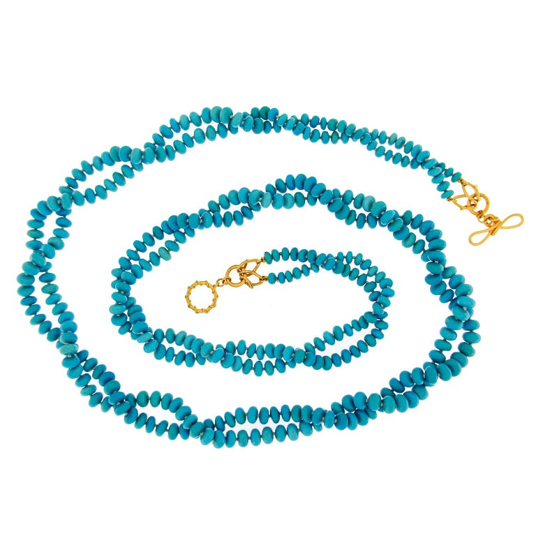 This Valentin Magro necklace is made of two strands of turquoise rondelles. It can be worn many ways, from as-is to looped around the neck, creating a field of blue.  A wire wrapped 18k yellow gold ring-and-toggle clasp featuring interlocking Vs