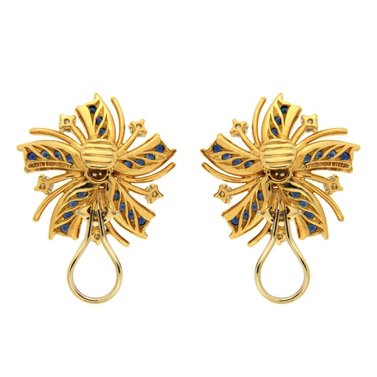 The Valentin Magro 'Viva El Sol' earrings are made in 18kt yellow gold, they feature round brilliant diamonds and round blue sapphires.  They are finished with clip backs. Measurement detail - width 29 mm, length 29 mm, depth 7 mm.