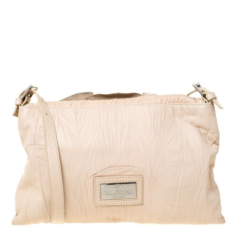 Bags like these are hard to come by, so quickly grab one when you can! Crafted from beige leather this bag by Valentino features a beautiful rose detailing on the front. Equipped with a shoulder strap, it has a front flap closure that opens to a