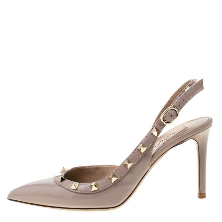 Create an aura of elegance with these lovely sandals from Valentino. These beige sandals are crafted from patent leather and feature a sophisticated silhouette. They flaunt pointed toes and are embellished with the signature Rockstuds. They come