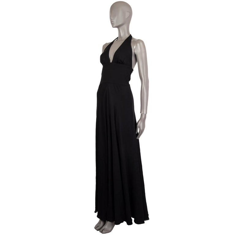 Valentino long evening dress in black missing tag (probably silk blend) with a slit in the front, halter neck closes two buttons and snap-buttons, deep cut-out and close fit around the waist, A-line skirt and an open back. Lined in black fabric