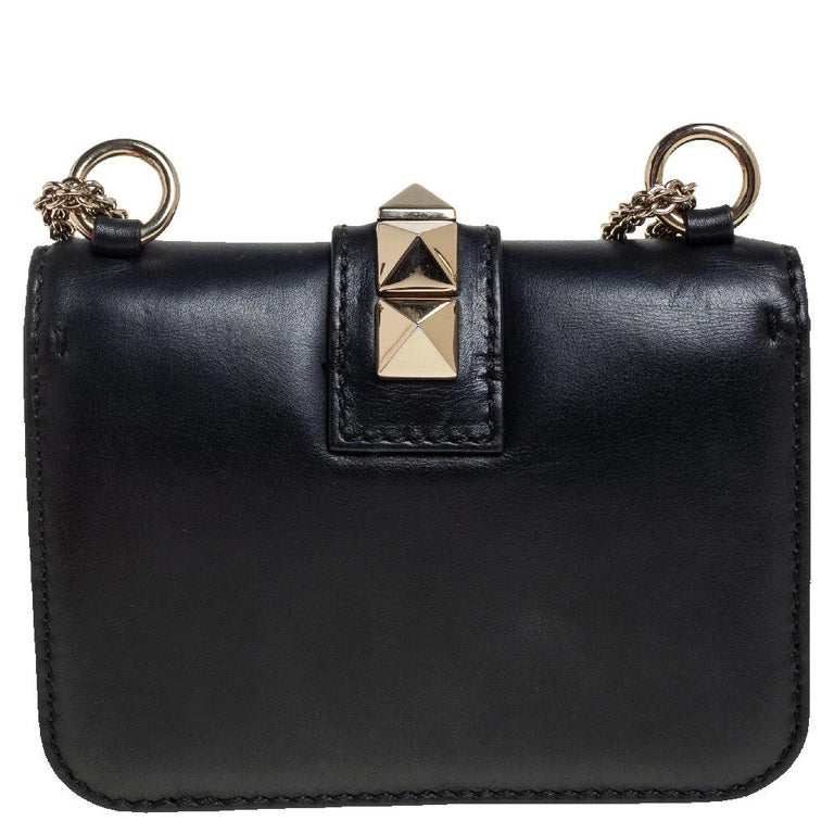 If you are looking for a bag with a blend of modern style and class, this Valentino creation is the answer. Crafted from leather, this black piece comes with a gold-tone chain and a flap with a push-lock to secure the well-sized fabric interior. The