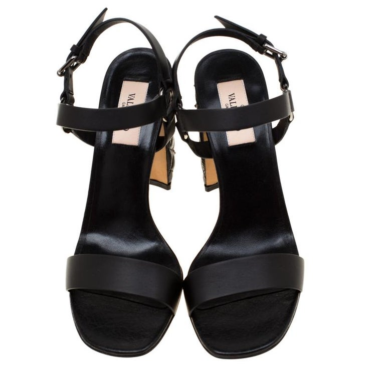 Simplicity is the ultimate sophistication, and these black block heel sandals remind one of exactly that. It is crafted impeccably from the finest leather and has an amazing Rockstud design that sets it apart. They come with ankle straps. These