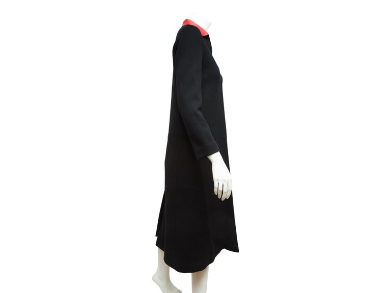 Product details:  Black long wool coat by Valentino.  Red spread leather collar.  Long sleeves.  Concealed front closure.  Center back hem vent.  Label size IT 40.  38