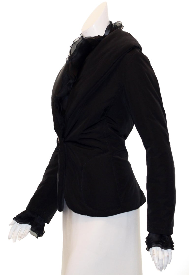 Valentino black puffer jacket decorated with 3 layers of ruffles on the collar, to the button closure and also around the cuffs.  This jacket has a dual personality, femininity and warmth.    This jacket is lined in Valentino black logo satin.   Two