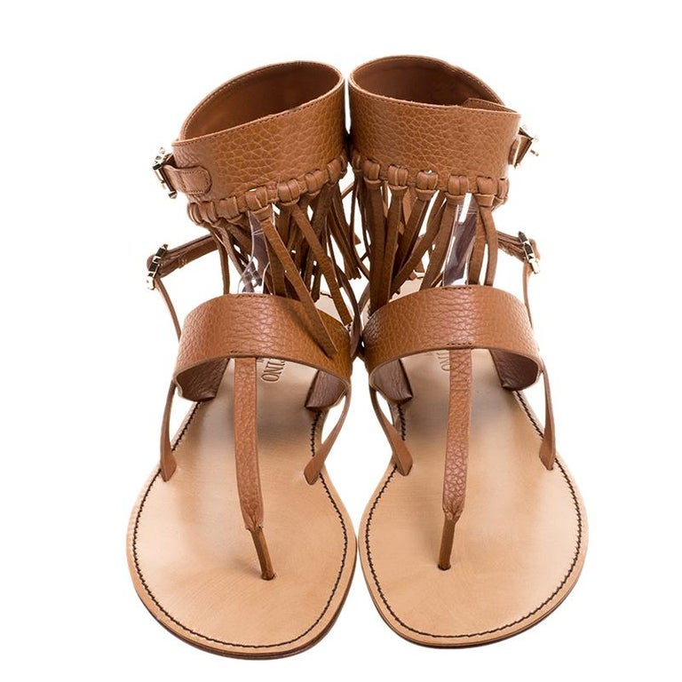 Coming from the house of Valentino, these sandals feature a brown leather fringe detail that lends it a Boho-chic vibe. It comes with an ankle wrap style strap secured with a gold-tone buckle. Wear with everything from fluid dresses to