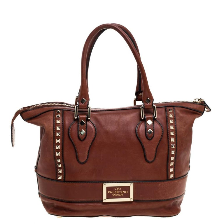 This brown leather tote from Valentino is classic and elegant. With gold-tone Rockstuds, bow detail to the front, and the brand label at the rear, this tote features a wonderful exterior. Fully lined with satin, the spacious interior has one zip and
