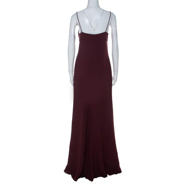 Sway like a dream in this evening gown from Valentino. Tailored to perfection, the burgundy gown has thin shoulder straps, a plunging neckline and a hemline that beautifully falls to the floor. Pair it up with simple heels, accessories and a