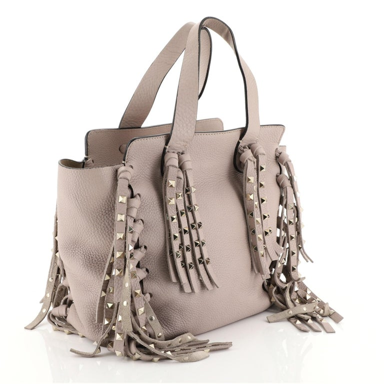 This Valentino C-Rockee Fringe Tote Leather Micro, crafted from neutral leather, features hand-knotted long leather fringes, dual flat leather handles, whipstitched base, and gold-tone hardware. Its zip closure opens to a neutral suede interior with