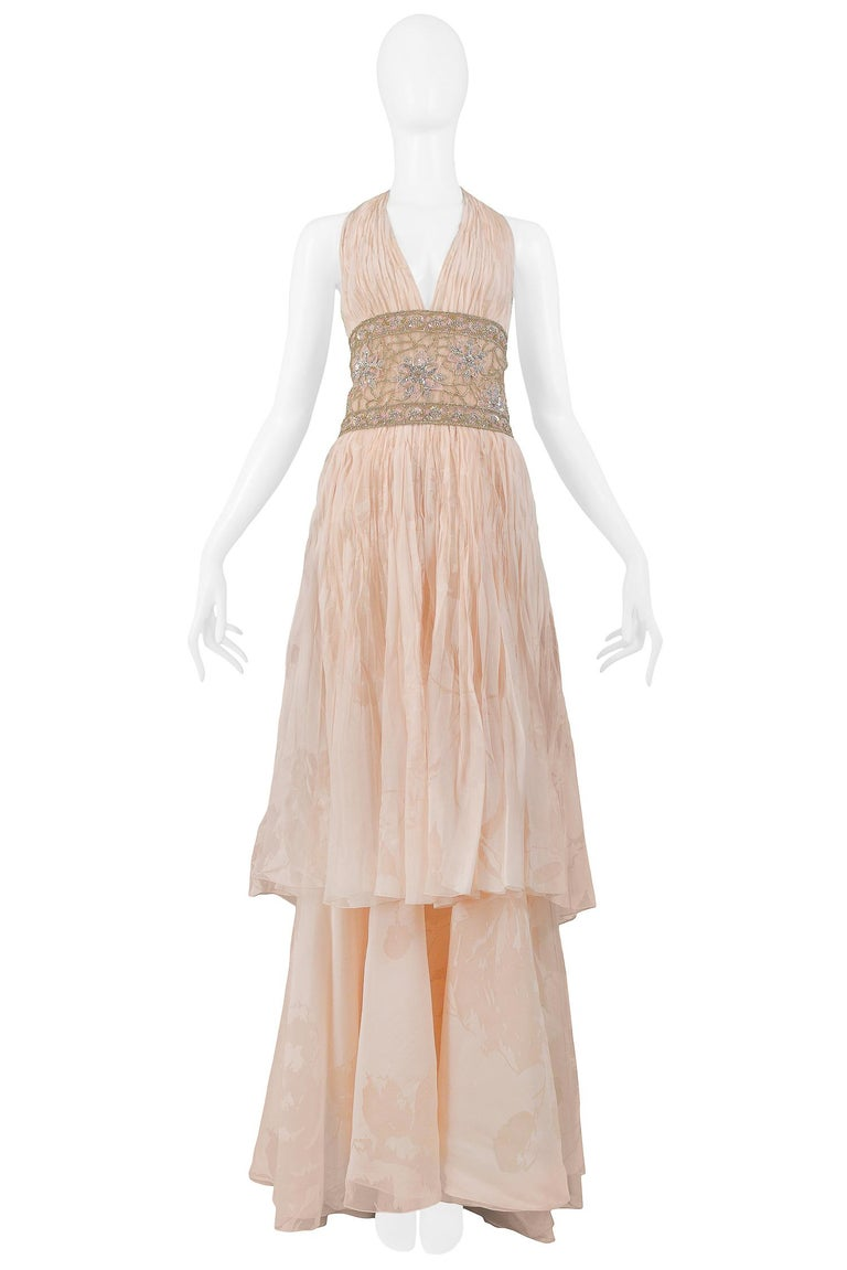 We are excited to offer a vintage Valentino Couture peach pink floral silk runway gown. The gown is 100% silk and features a halter style V-neckline with accordion pleating,  two-tiered skirt, slight train, a side zip closure, and a handmade gold
