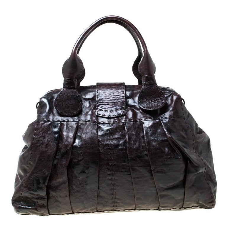 This dark brown satchel from Valentino will give you days of style and ease. It is crafted from leather and features a flap strap that holds the brand's V logo. It is equipped with a spacious canvas interior, two handles and a shoulder