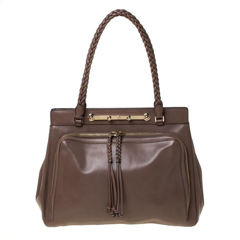 This exquisite creation from the house of Valentino is sure to win hearts. Featuring an angular shape, this Demetra tote is made from grey leather and is beautified a zipped pocket that is placed at the front. It features two braided top handles and