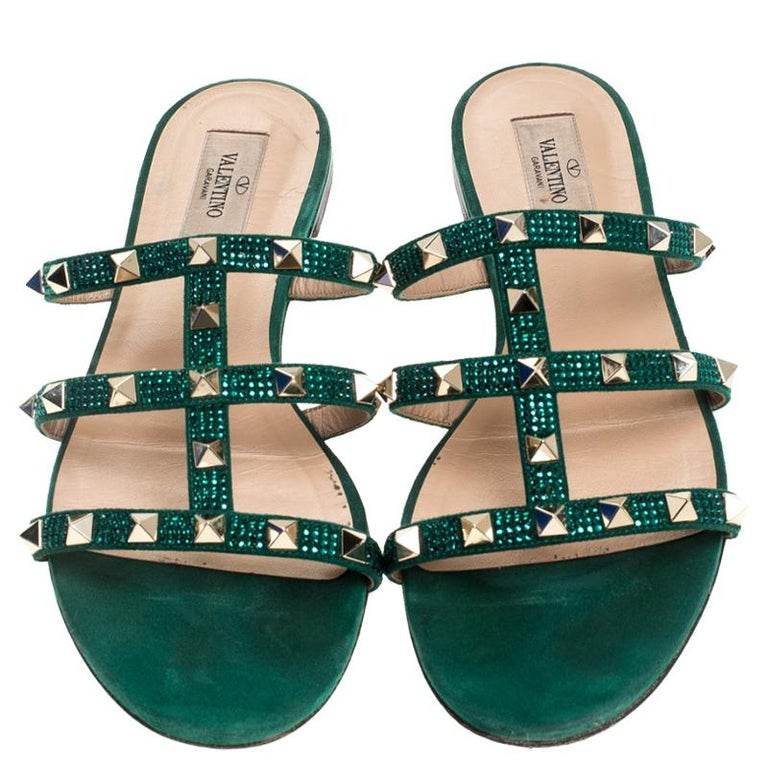 These Valentino slides feature a gorgeous design of suede straps detailed with the signature Rockstuds and crystals. Easy to slide it on and off, these pair makes a great accompaniment to dresses and skirts alike.