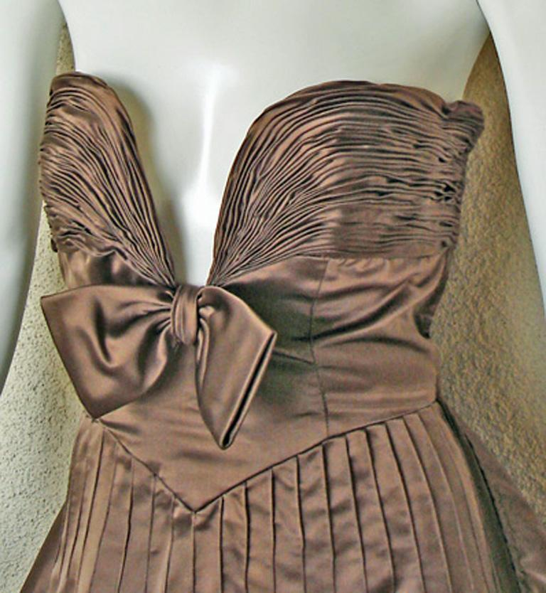 An original Valentino Garavani original runway gown.  Fashioned of rich copper brown duchess satin with plunging fitted bodice accented with hand pleated detail and center bow adornment.  Seath silhouette with long dramatic swantai train.  A
