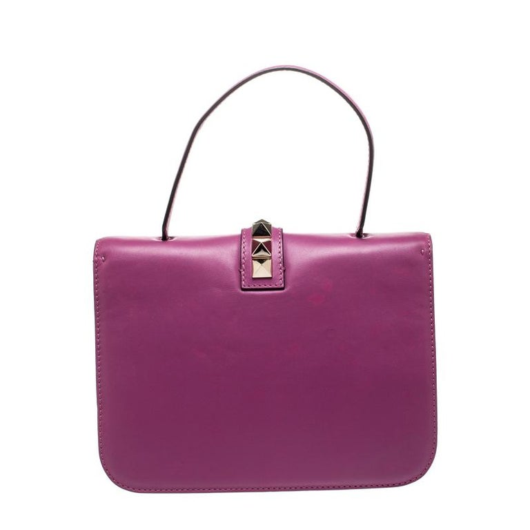 If you are looking for a bag with a blend of modern style and class, this Valentino creation is the answer. Crafted from leather, this purple piece comes with a flat top handle and a flap with a push-lock to secure the well-sized fabric interior.
