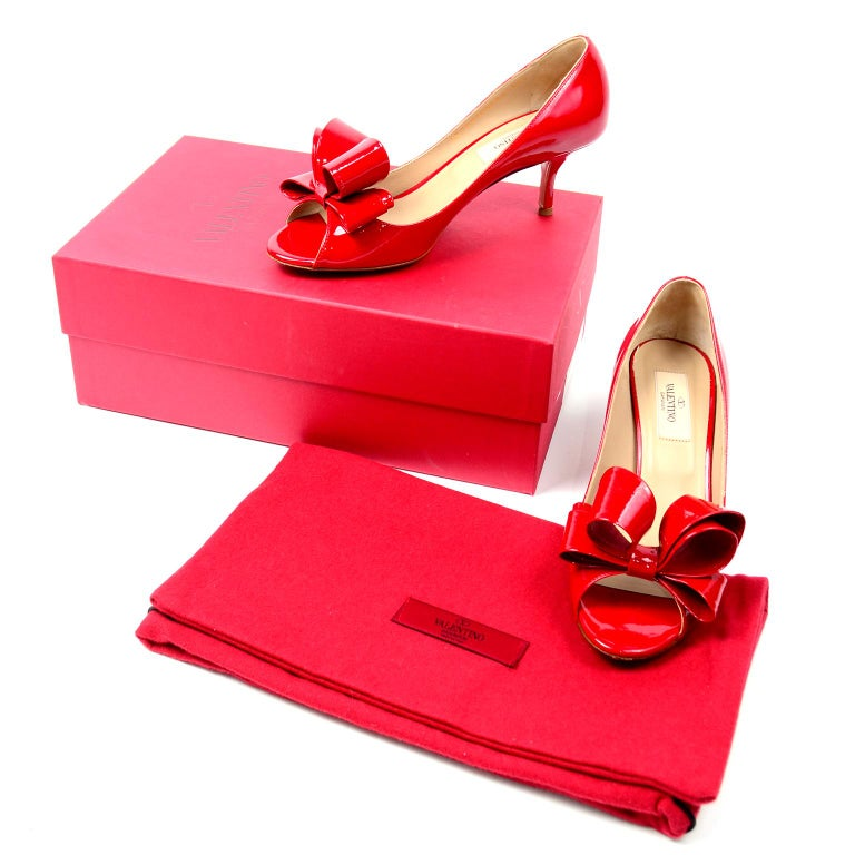 These fabulous iconic Valentino bow pumps are entirely crafted from a cherry red patent leather. These peep toe shoes have beautiful beige leather interior and sole. We love the structured bow that makes these shoes stand out. These shoes come with