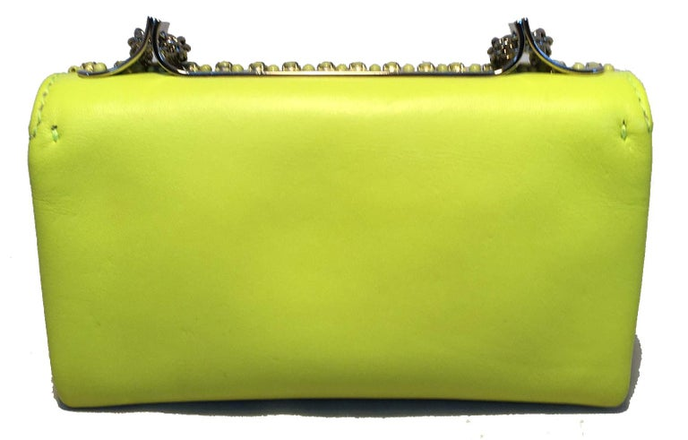 Valentino Garavani Va Va Voom Neon Studded Knuckle Clutch with Strap in excellent condition. Neon yellow/lime green leather and studded exterior trimmed with silver hardware and chain shoulder strap. Unique knuckle front handle to use as clutch.
