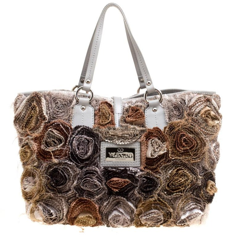 Set in a contemporary design and style, this flower tote from Valentino is absolutely mesmerizing. The lovely tote features beautiful fabric flower appliques all over it. It comes with dual leather handles, a spacious satin-lined interior to house
