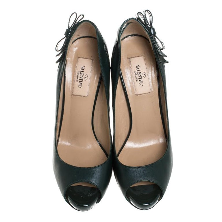 Work your magic while donning this pair of pumps from the iconic house of Valentino. Crafted in Italy, they are made from leather and patent leather. These green pumps are styled with peep toes, 12 cm heels, platforms and bow detailing near the