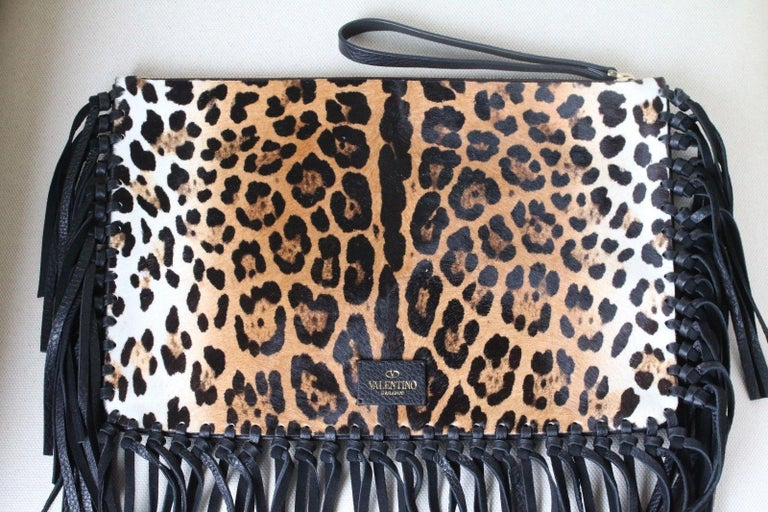 Fun fringe lends eye-catching appeal to this luxe calfskin clutch from Valentino. Animal print calfskin, black fringed trim, top zip with pull, inside back wall zip pocket. Calfskin/Leather.  Dimensions: Approx. 14 x 9 x 0.5 inches  Condition: New