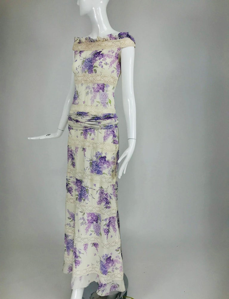 Valentino lilac print silk and lace maxi dress with very long ties at the lower waist back, we have wrapped them around the hip. This lovely dress rides the shoulder edge with a ruffle of silk and lace. The dress is done in wide alternating bands of