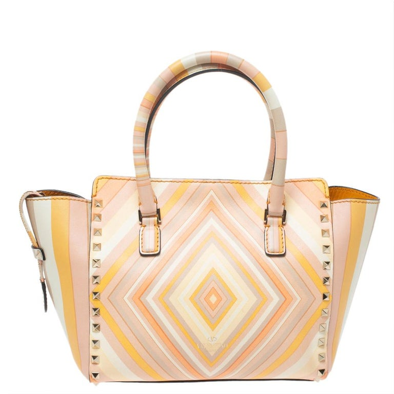 This Rockstud bag from Valentino is crafted with finesse and is made for a fashionista like you. It features the signature Native Couture 1975 multi-color print and beautifully placed gold-tone studs. This tote bag comes with an extra studded strap