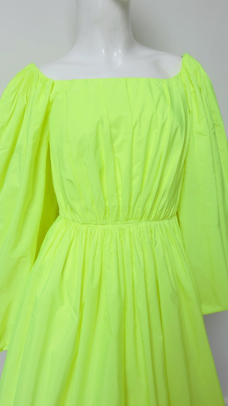 An incredible neon yellow green dress from Valentino.  It has a scoop neckline, full sleeves, a full skirt, and a fitted waist. It is lined in the same fabric and has a back zipper.   Fits sizes Small, Medium.  Bust  36