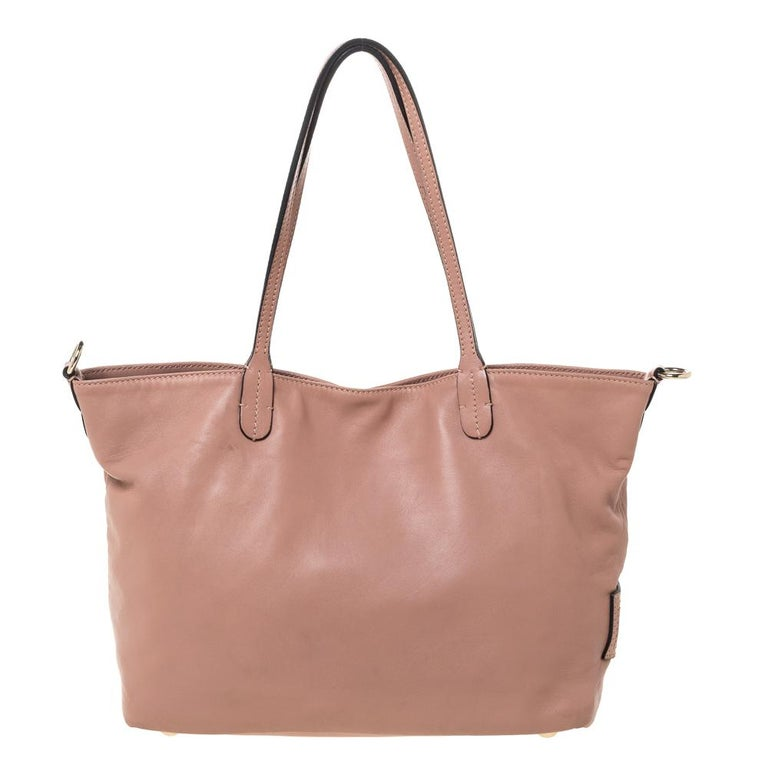 Valentino is known to bring out unique and one-of-a-kind pieces year after year and this tote is indeed one of them! It is crafted beautifully from old rose leather with flower appliques on the front and a brand label plaque on the side. It comes
