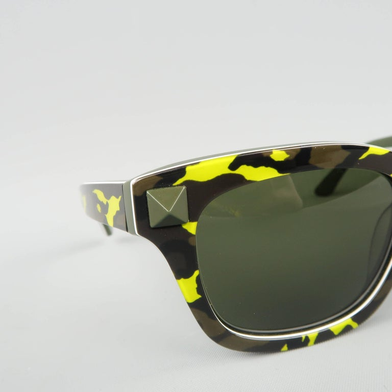 VALENTINO wayfarer sunglasses come in olive and lime green camouflage print acetate with black lenses and olive pyramid stud detail. Made in Italy.   New with Tags. Retails at $375   Measurements:   Length: 15 cm. Height: 5 cm.
