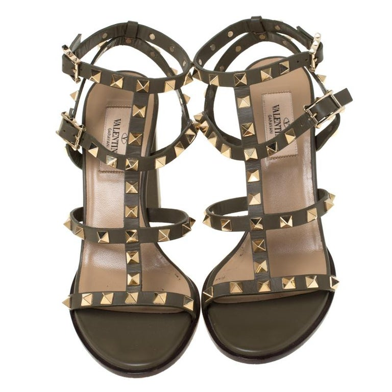 Adorned with signature Rockstuds, this pair of sandals by Valentino are elegantly designed to exude an aura of sophisticated style. Crafted into a chic cage silhouette and fitted with block heels, these shoes can perfectly match your party ensemble