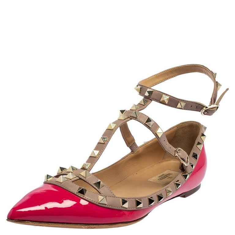 Valentino Rockstud ballerina in pink patent leather. The flats feature pointed toes, buckle fastening, and signature studs on the beige straps.