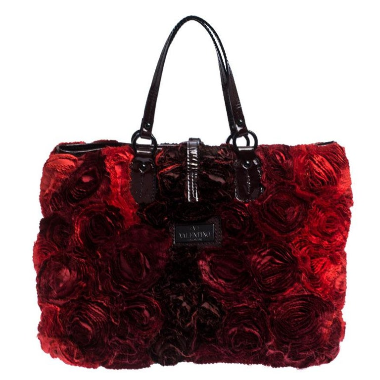Valentino is known to bring out unique and one of a kind pieces year after year and this bag is indeed one of them! It is crafted from red leather and features an artistic silhouette. It flaunts a flower applique detailing all over and a black-tone